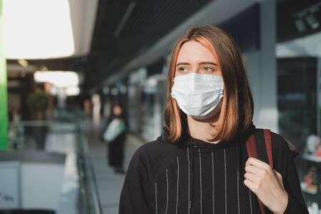 142290380-woman-in-a-protective-face-mask-at-a-shopping-mall-coronavirus-covid-19-spread-prevention-concept-re